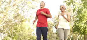 Senior Couple Jogging In Park Smiling